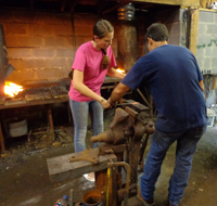 Brad Greenwood teaching blacksmith techniques to an eager student.